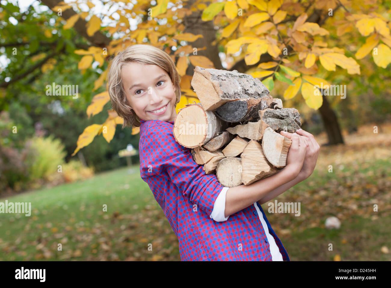 Germany, Leipzig, Boy holding firewood, smiling - Stock Image