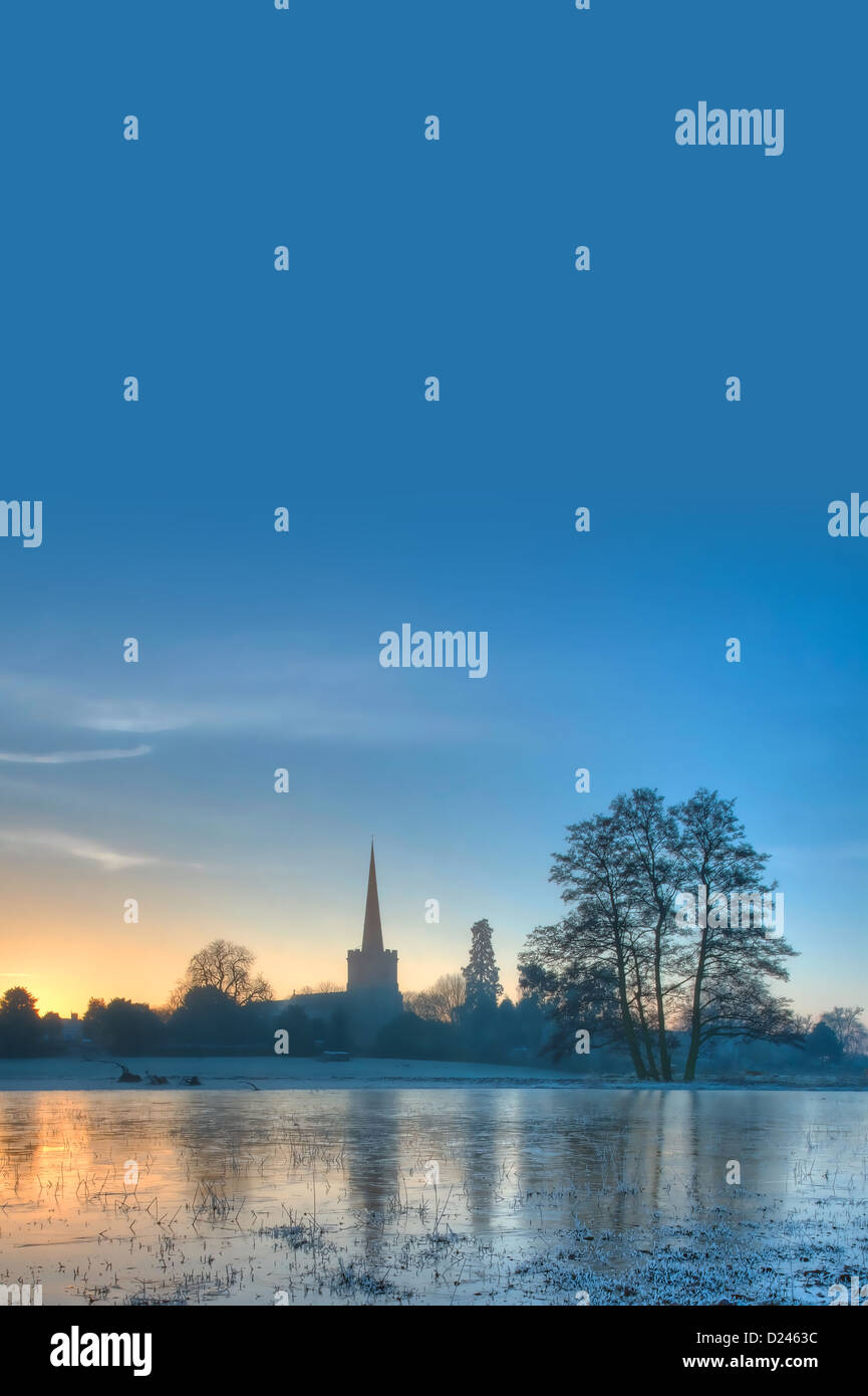 Winter background with church at sunrise - Stock Image