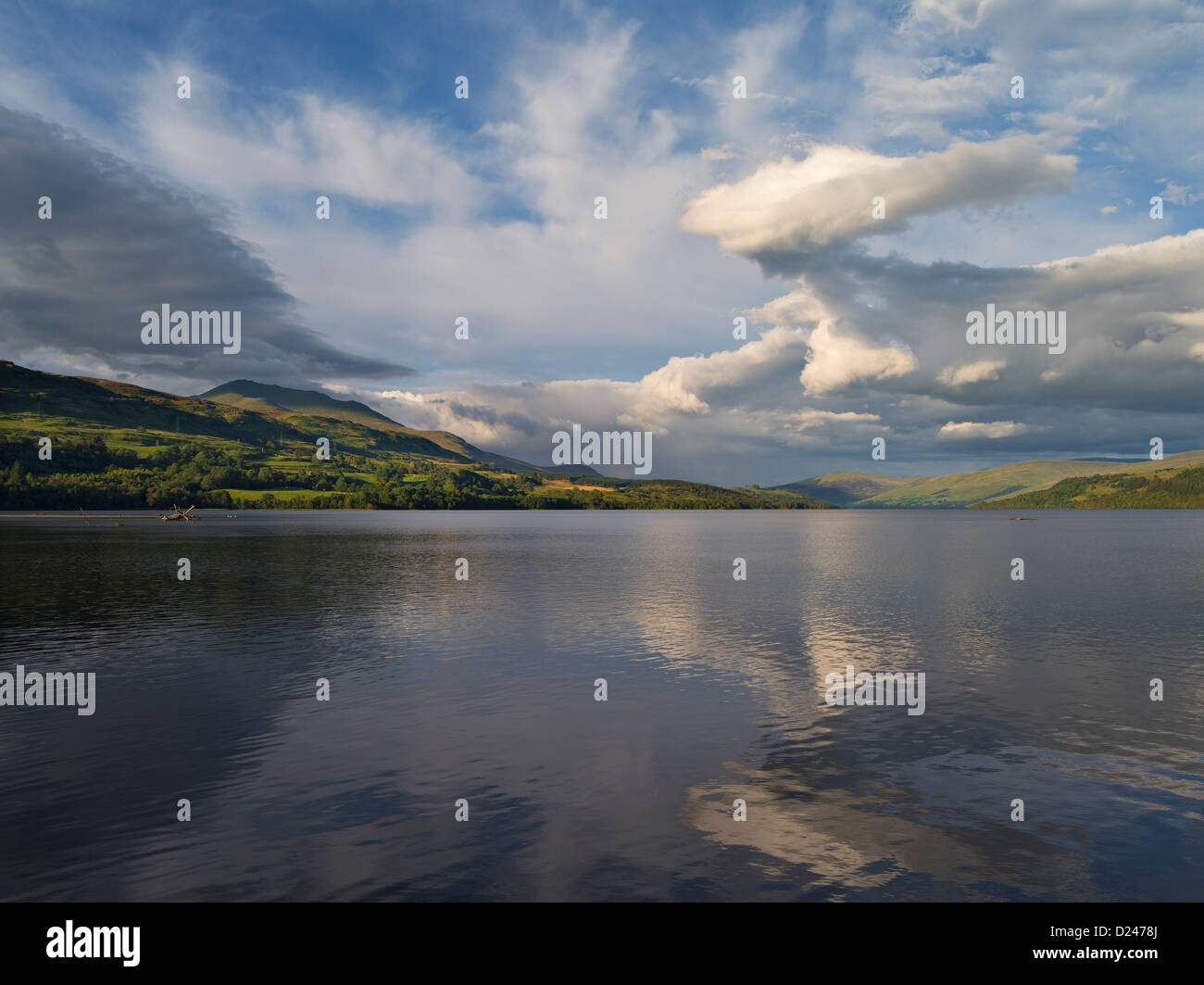 Evening thunderhead cloud rises over calm lake with distant hills - Stock Image