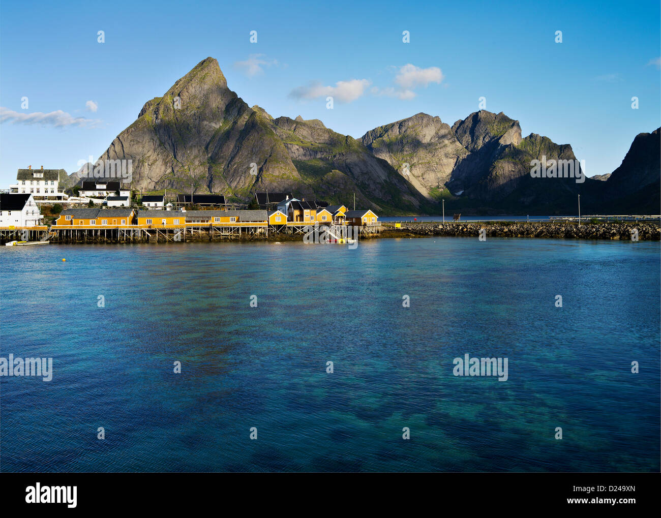 Cabins and stores on the island of Sakrisoy under the dramatic peak of Olstinden, Lofoten, arctic Norway. Stock Photo
