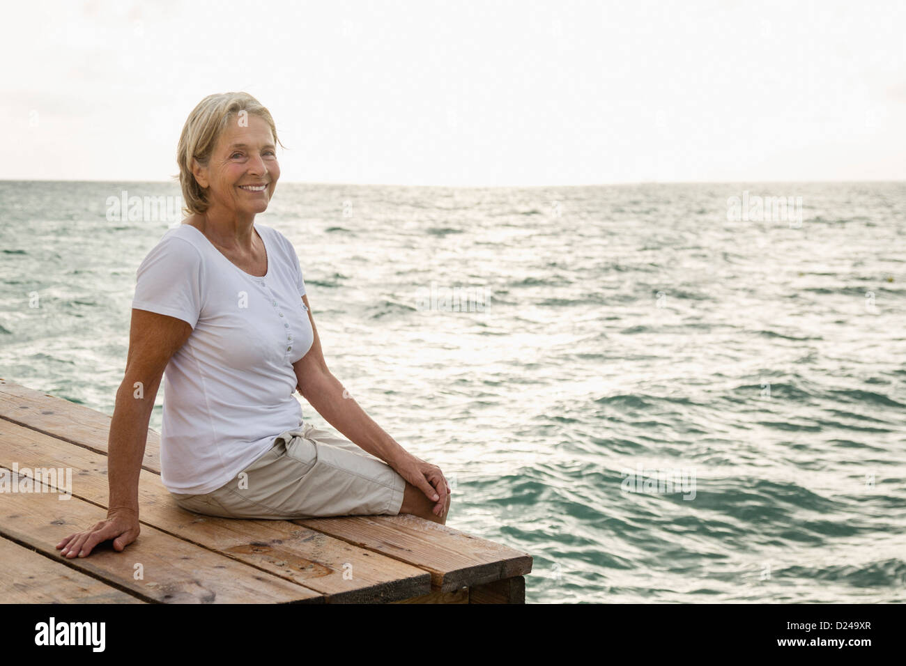 Spain, Senior woman sitting on jetty at the sea - Stock Image