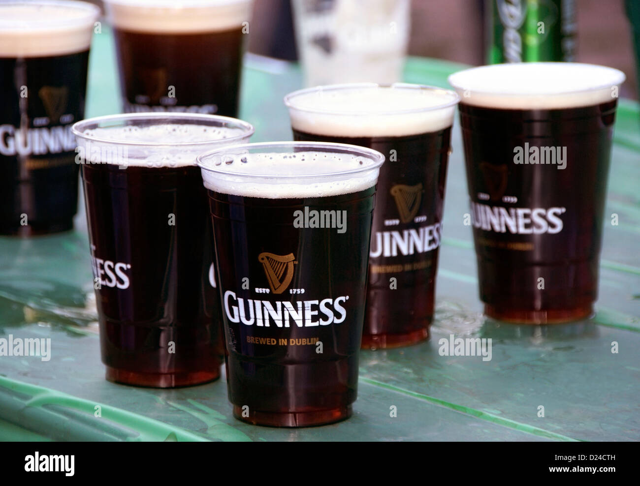 Guinness beer cups on a green table during St. Patrick's day celebration - Stock Image