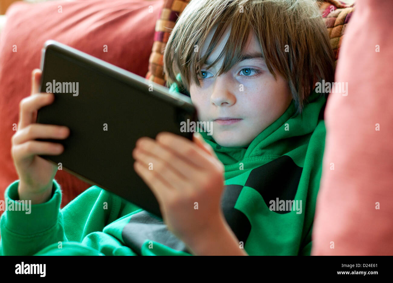 young male boy using ipad mini tablet computer Stock Photo