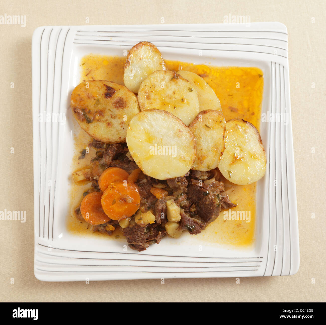 A homemade stew of beef, onion, carrots and parsnips, made in a pressure cooker, served with sliced sauteed potatoes - Stock Image