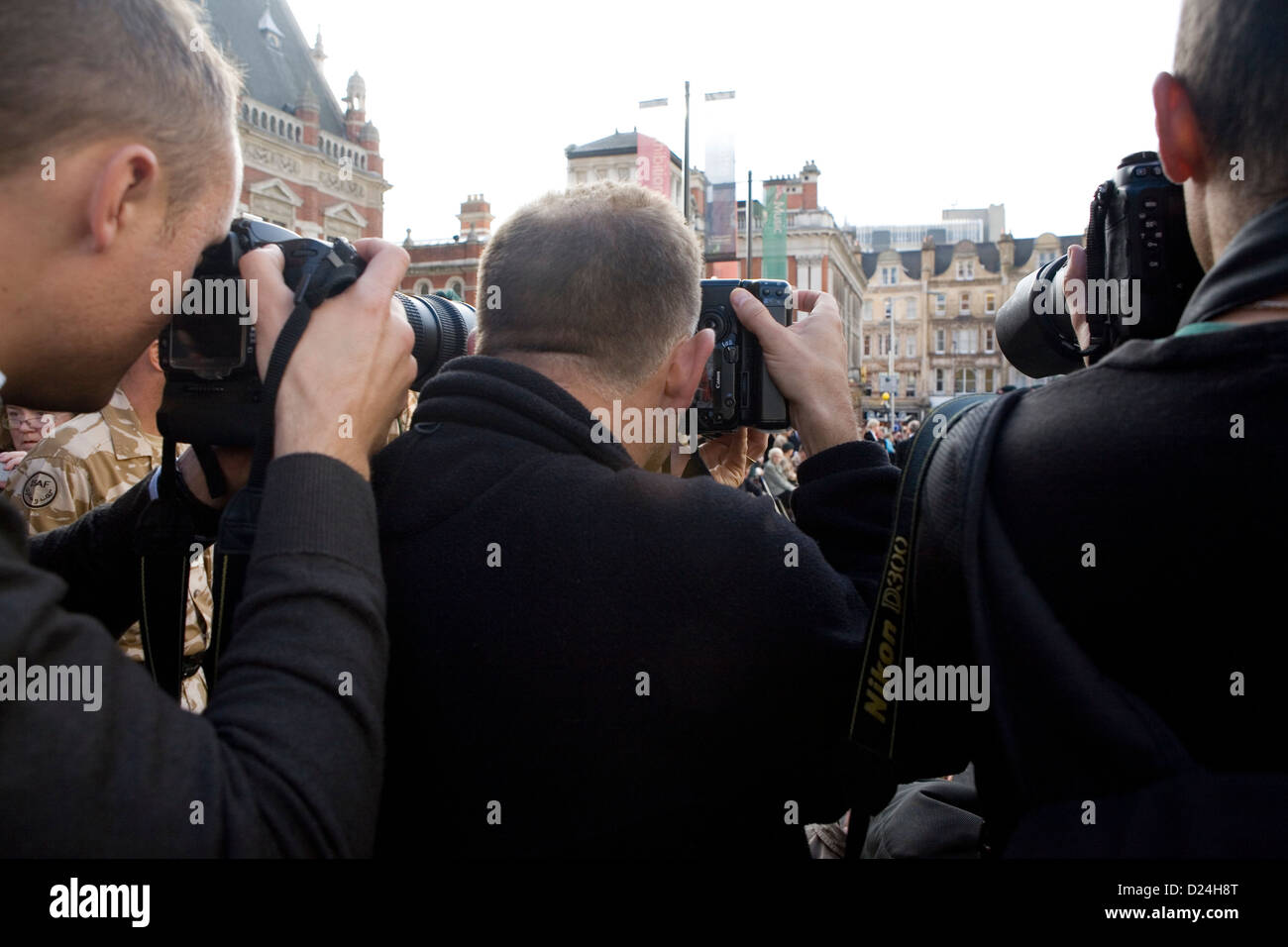 The backs of a group of photographers at a welcome home parade for British soldiers. Stock Photo