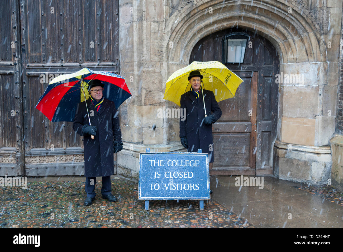 Cambridge UK 14th January 2013.  Porters shelter from the snow under umbrellas outside Trinity College Cambridge. - Stock Image