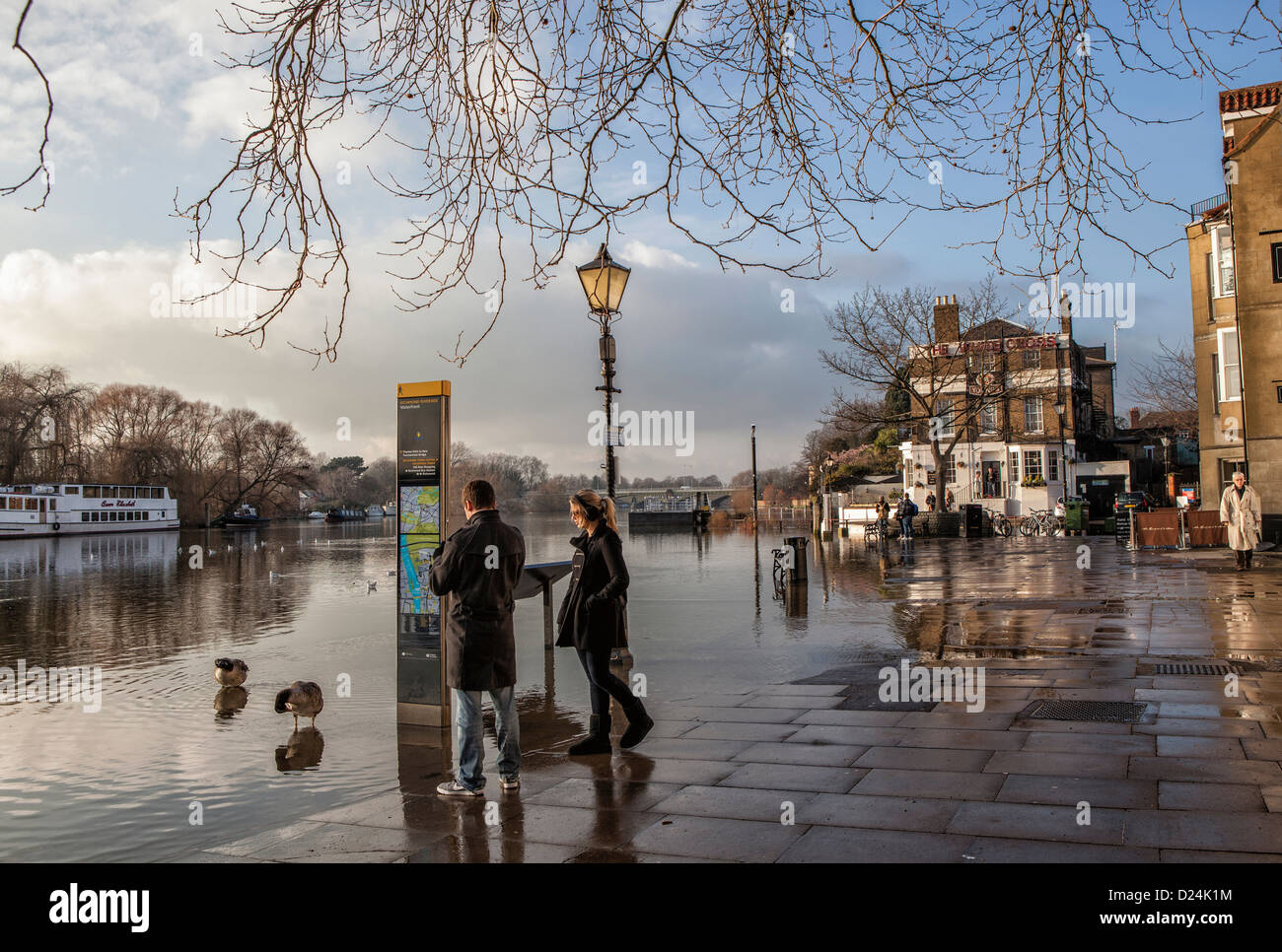A man and a woman watch the rising water of the Thames river at high tide - Richmond upon Thames, Surrey - Stock Image