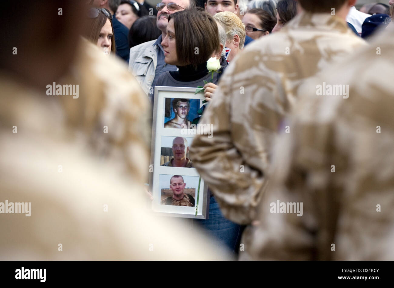 The relatives of dead British soldiers hold up their photos at a welcome home parade for soldiers returning from - Stock Image