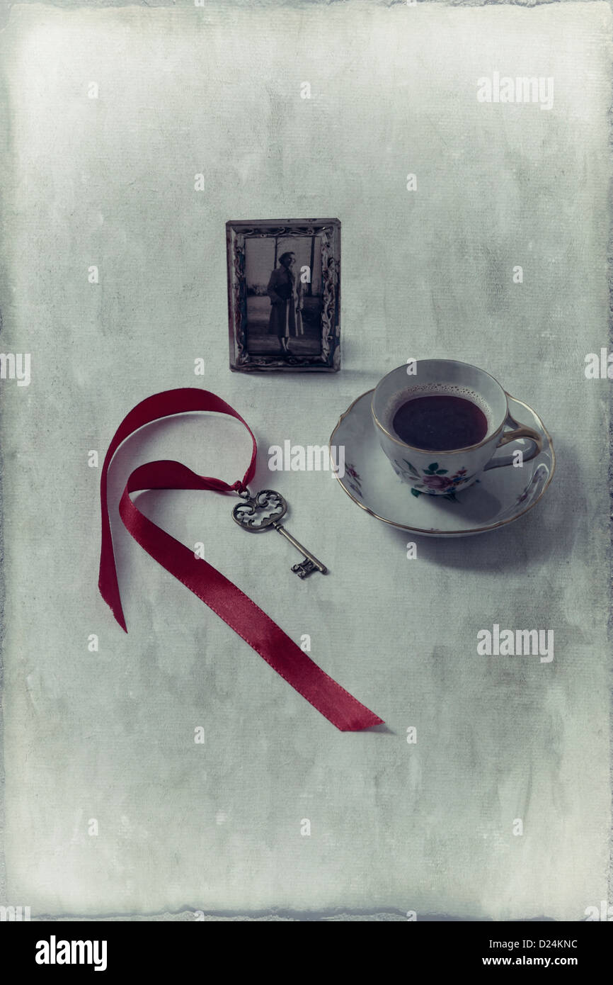 a cup of coffee with an old photo and an old key - Stock Image