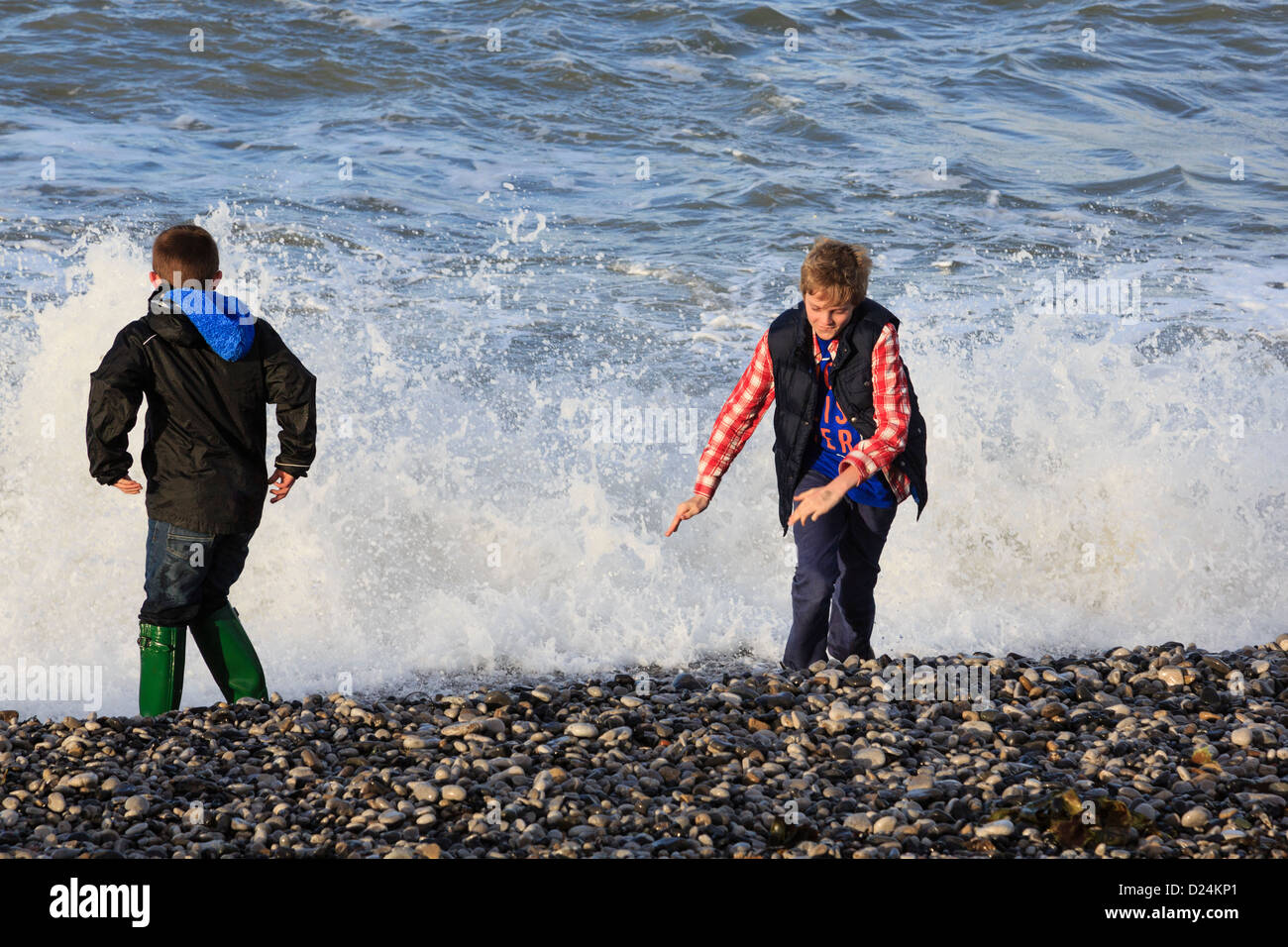 Two boys enjoy playing by the splashing waves at water's edge on Penmon beach on Isle of Anglesey, North Wales, Stock Photo