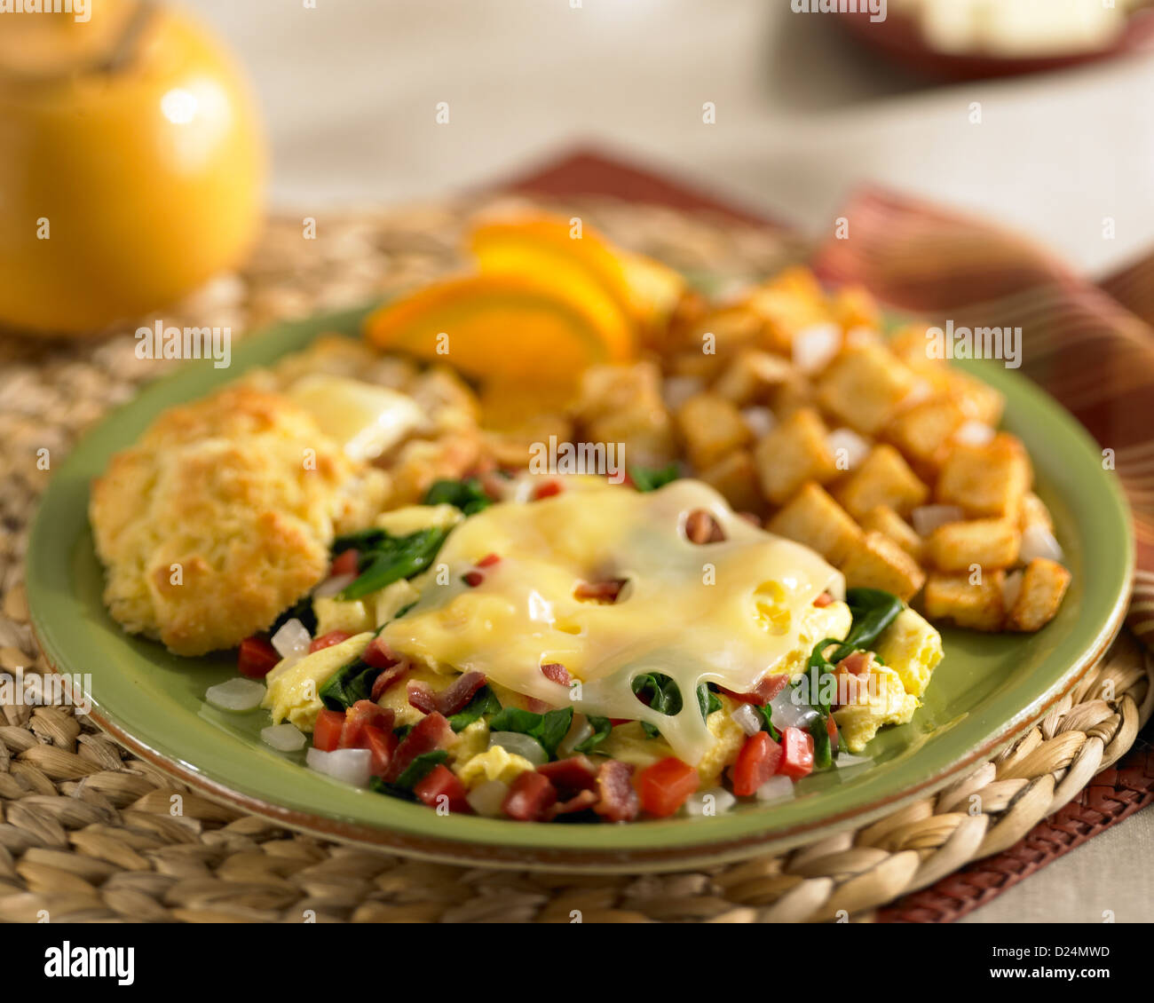 Spinach bacon scramble with melted swiss cheese served with potatoes and a biscuit with melted butter Stock Photo