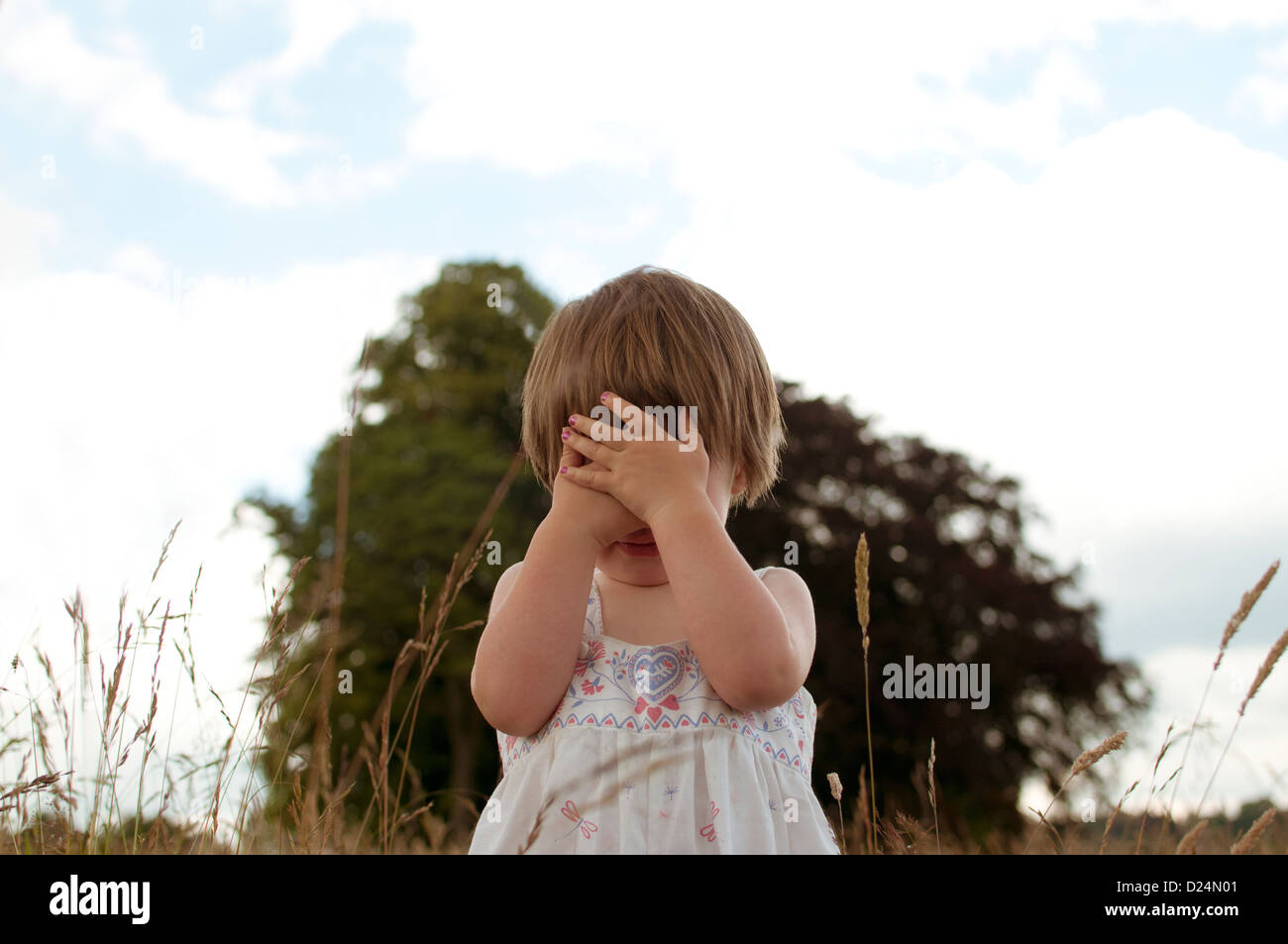 A little girl playing hide and seek outdoors - Stock Image