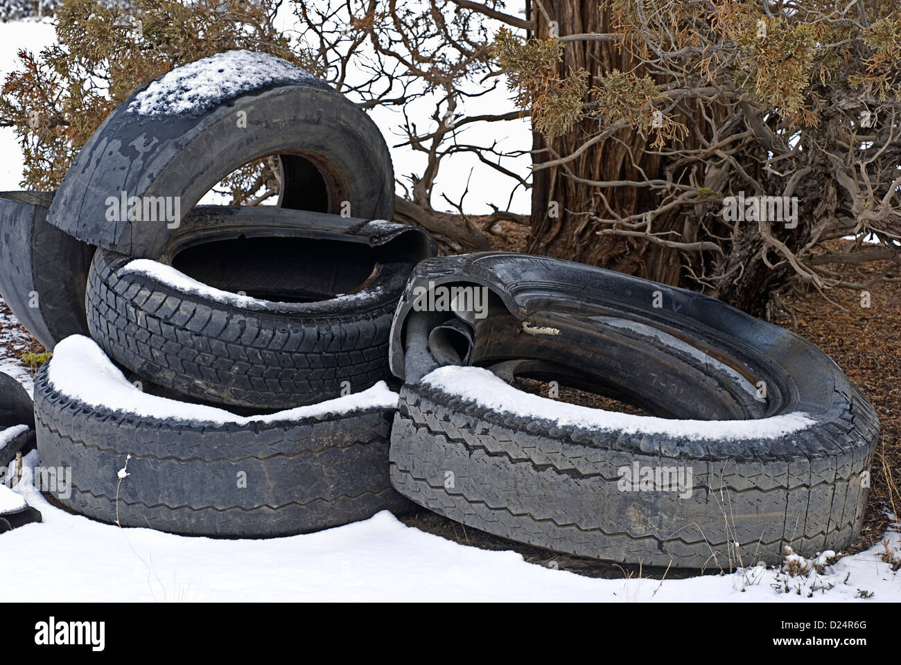 A pile of destroyed tires dumped on public lands, littering the landscape. - Stock Image