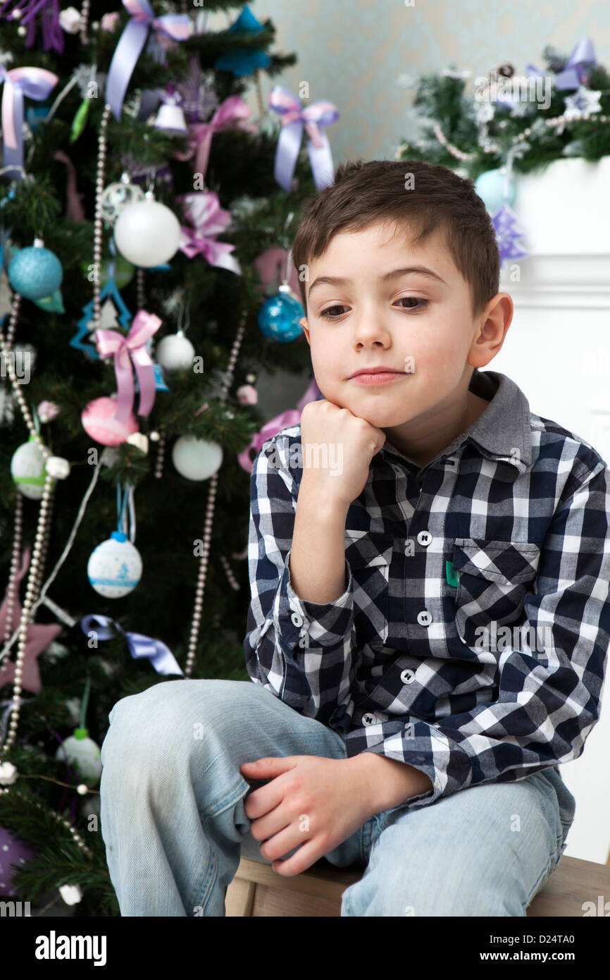 thoughtful boy six years old in a plaid shirt sitting around the Christmas tree Stock Photo