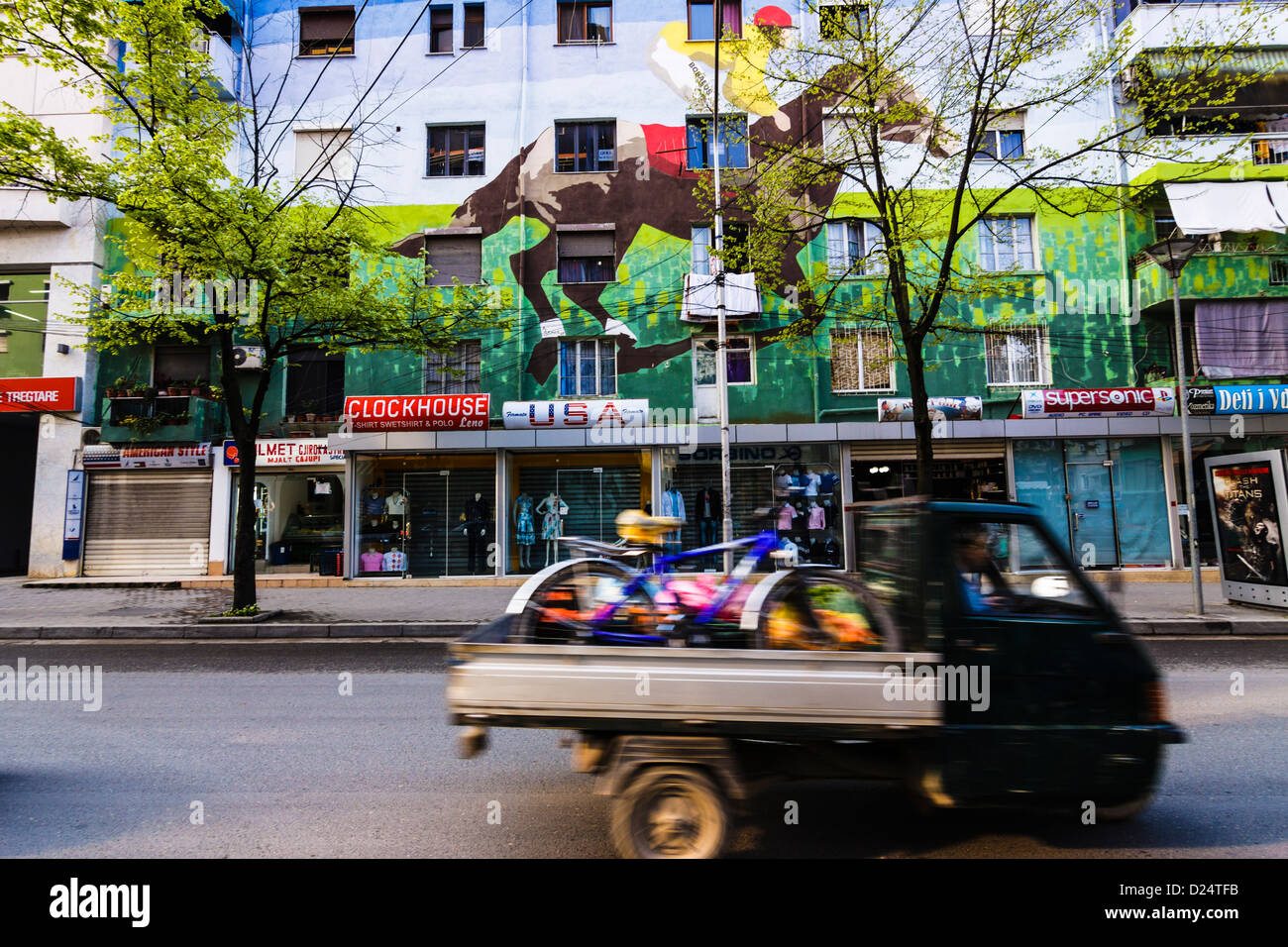 Tricycle van passing fast by horse with jockey wall painting in central Blloku district of Tirana , Albania - Stock Image