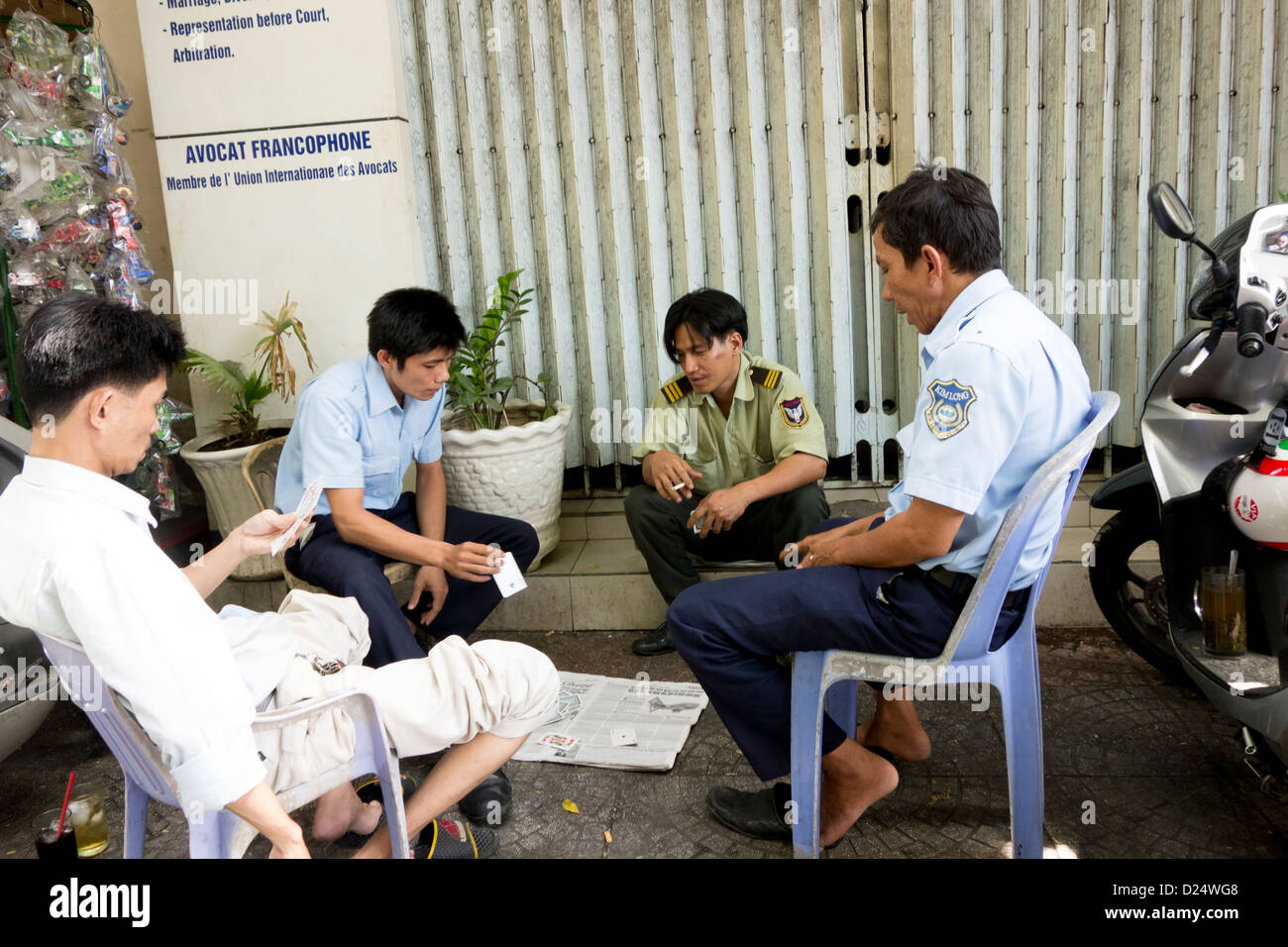 Vietnamese men play cards in street card game; Ho Chi Minh City; Vietnam South East Asia - Stock Image