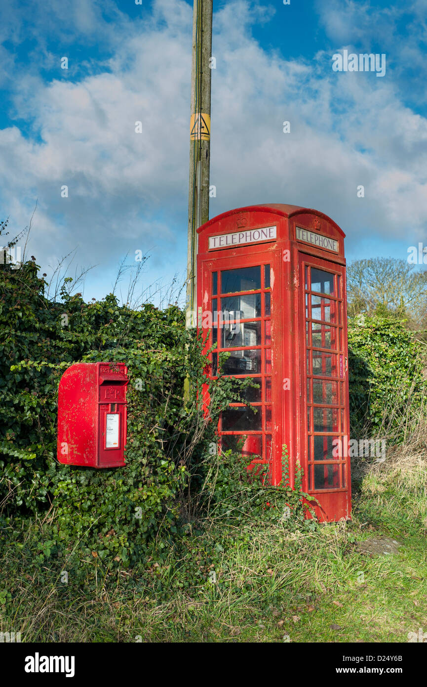 Unkempt, overgrown, red, BT Telephone Box - Stock Image