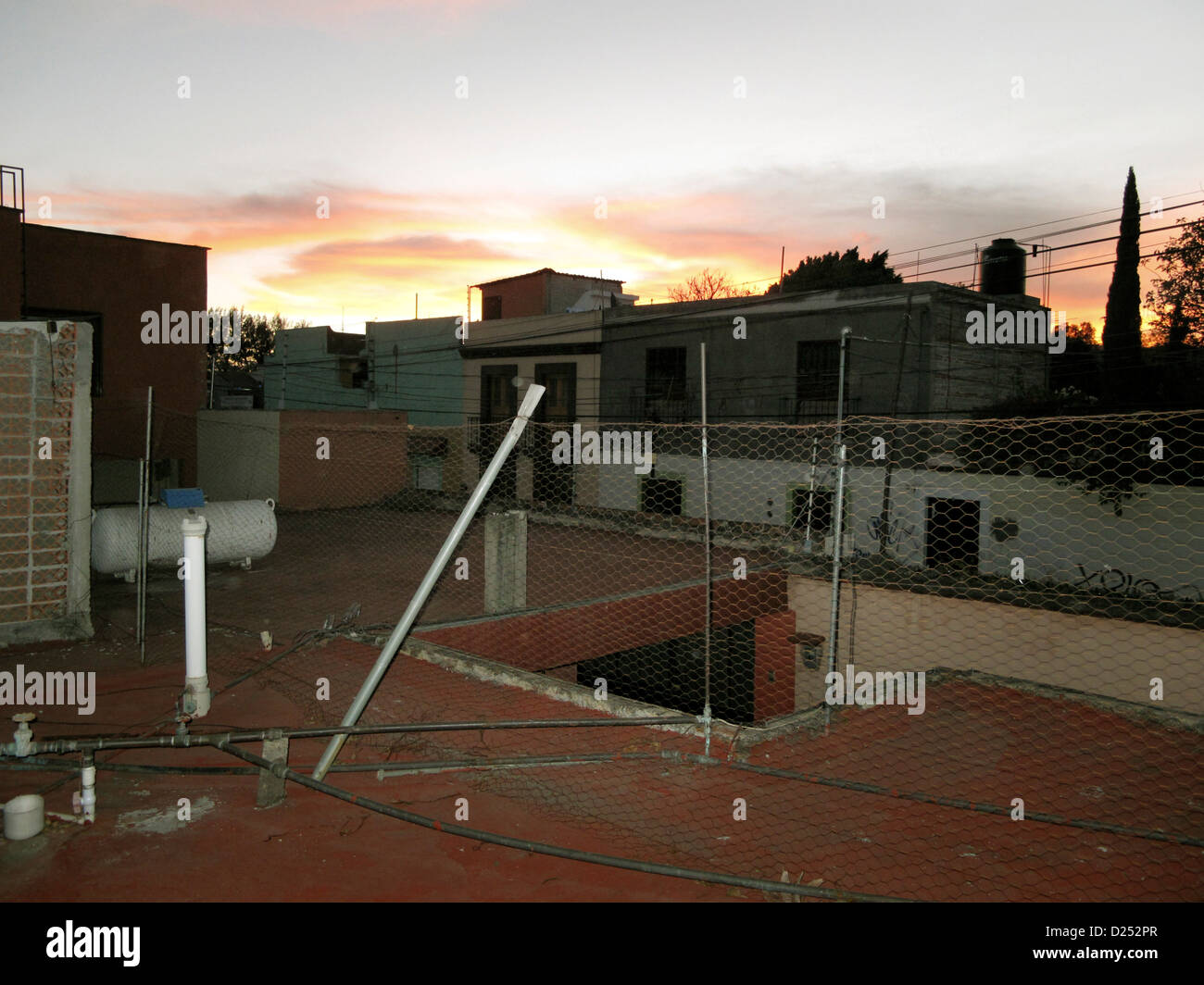 ordinary utilitarian rooftop in Oaxaca de Juarez at dusk with superb view of lingering sunset colors outlined buildings - Stock Image