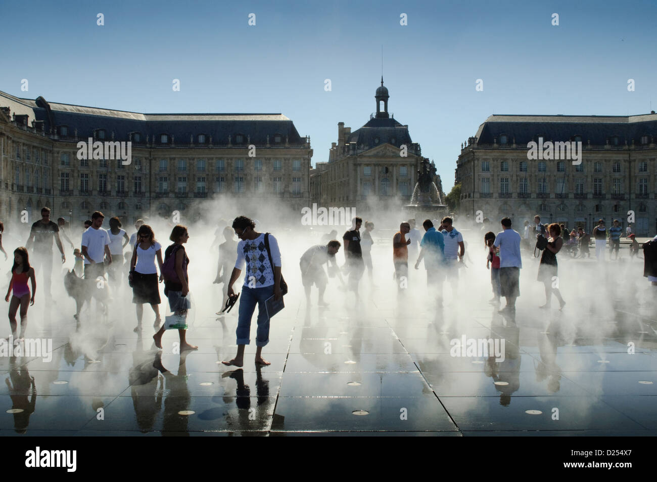 People walking in the spray from the words largest water mirror at the Place de la Bourse, Bordeaux, France - Stock Image
