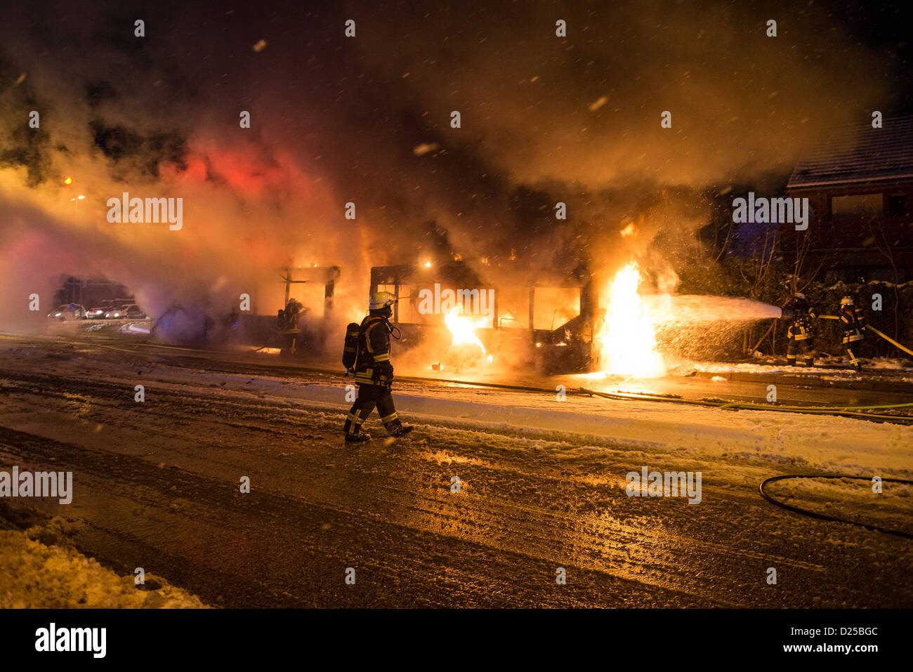 Firemen extinguish a burning bus in Flensburg, Germany, 14 January 2013. According to police reports, no one was - Stock Image