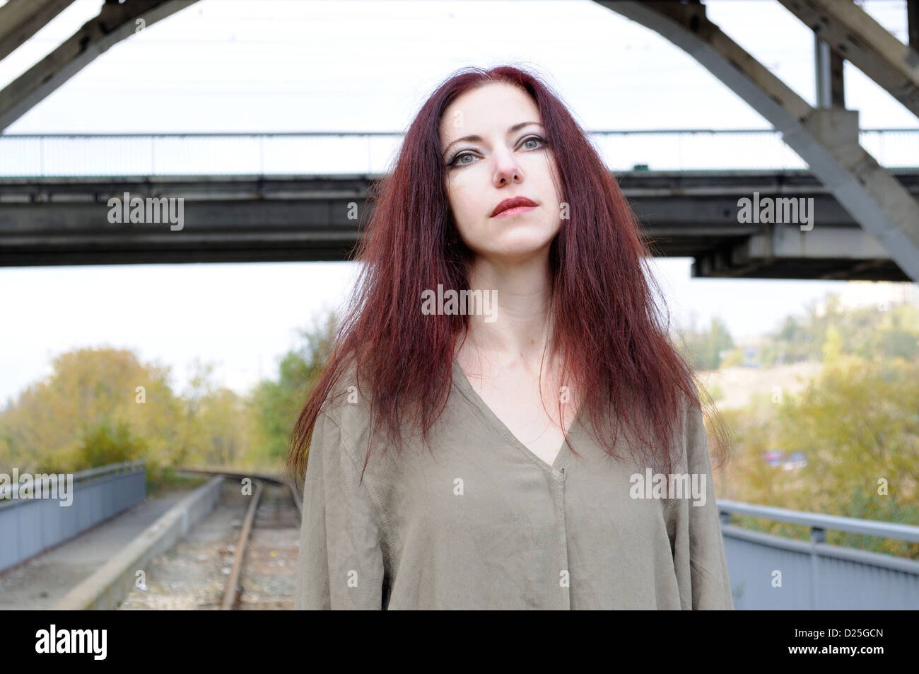 Sad woman in loose tunic against railroad track under a bridge - Stock Image
