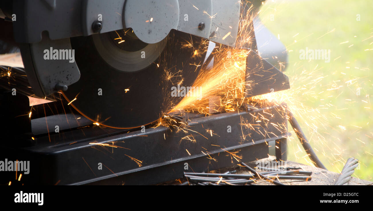 A worker operating a grinder. - Stock Image