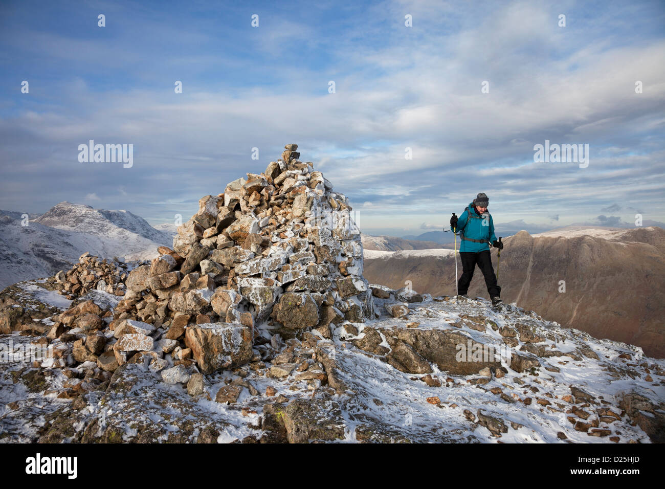 Walker on the Summit of Pike of Blisco in Winter with the Mountain of Bow Fell to the Left of the Cairn Lake District Stock Photo