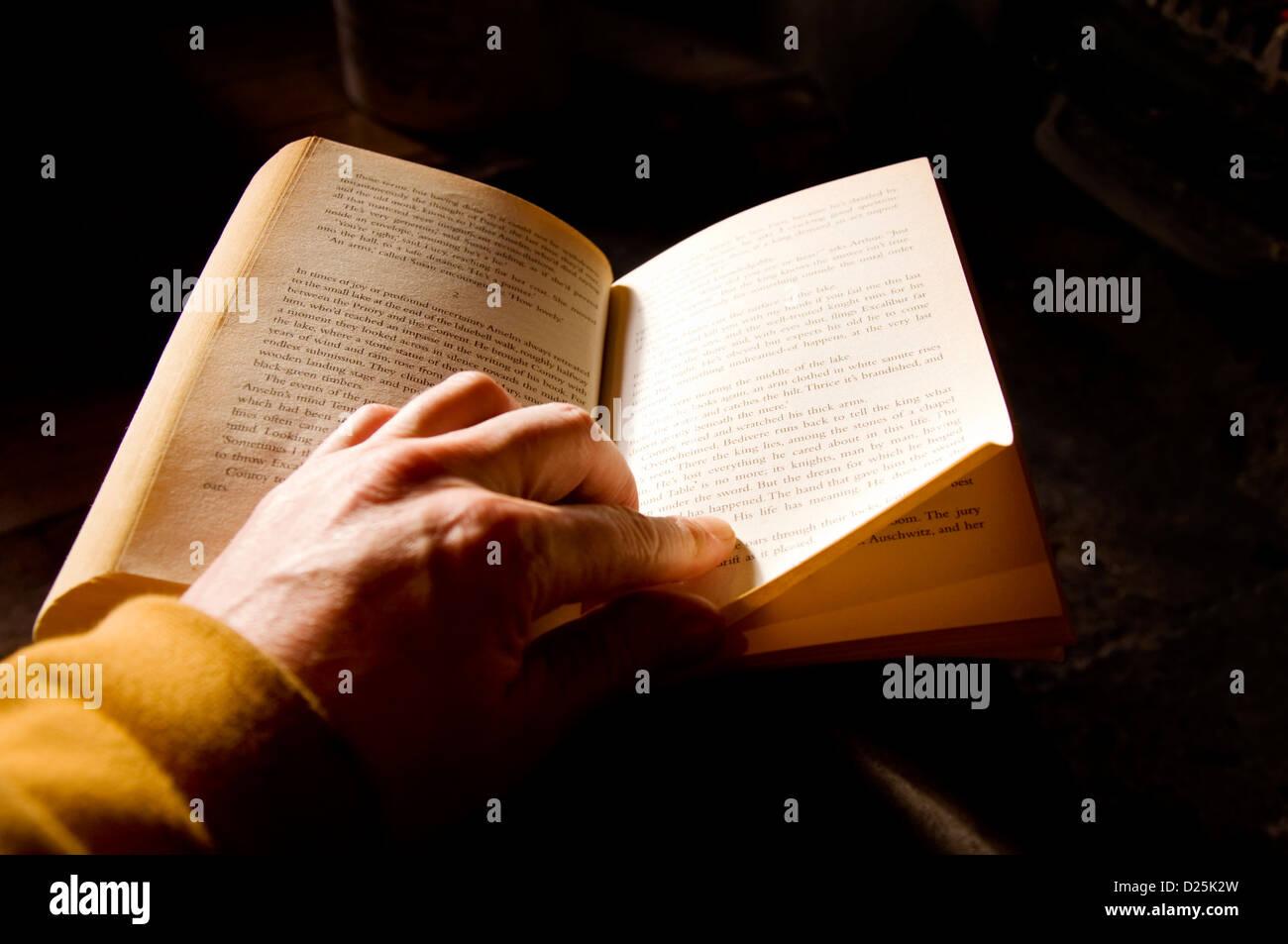 Reading a paperback novel - Stock Image