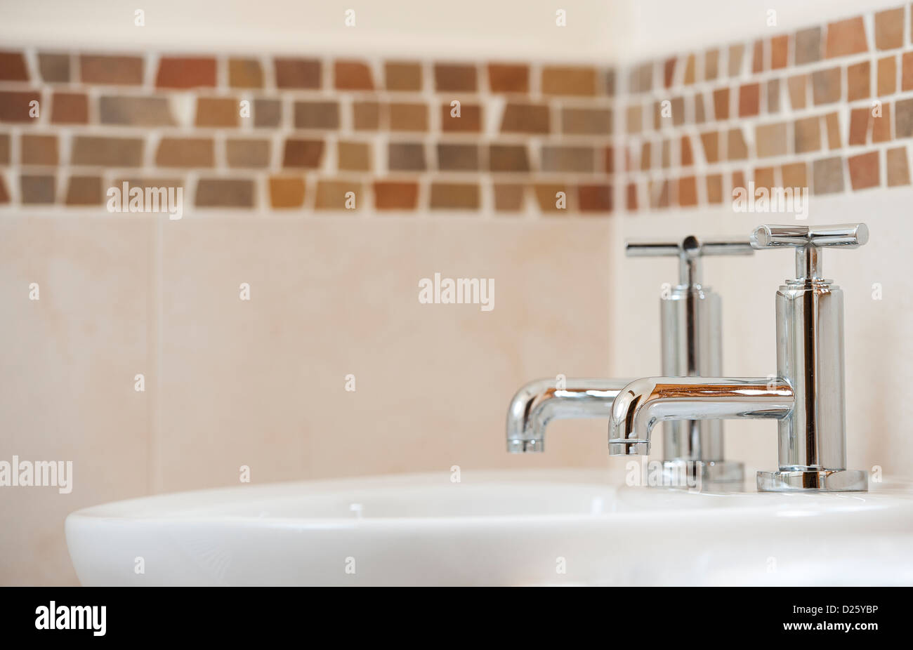 Close up of taps on a wash basin in a modern bathroom in a newly converted barn. - Stock Image