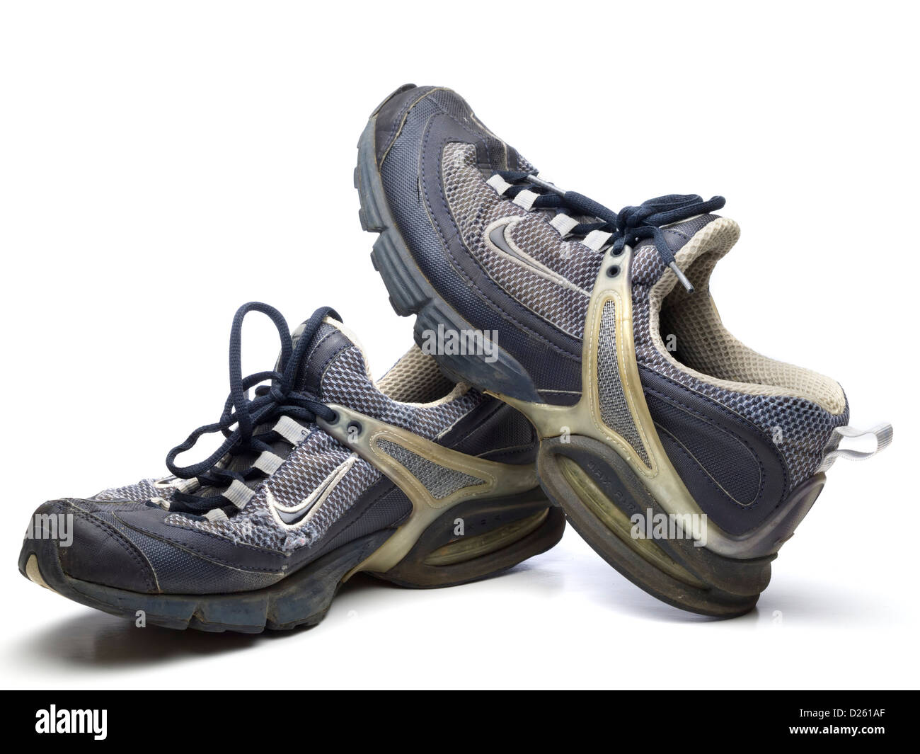 One pair of old blue Nike running shoes isolated on white background - Stock Image