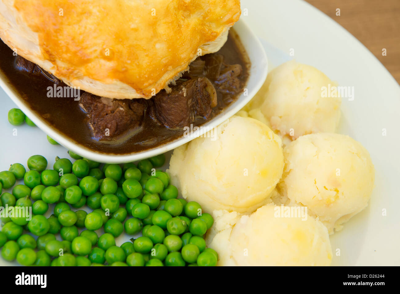 Tasty looking meat pie served with mashed potatoes and peas. - Stock Image