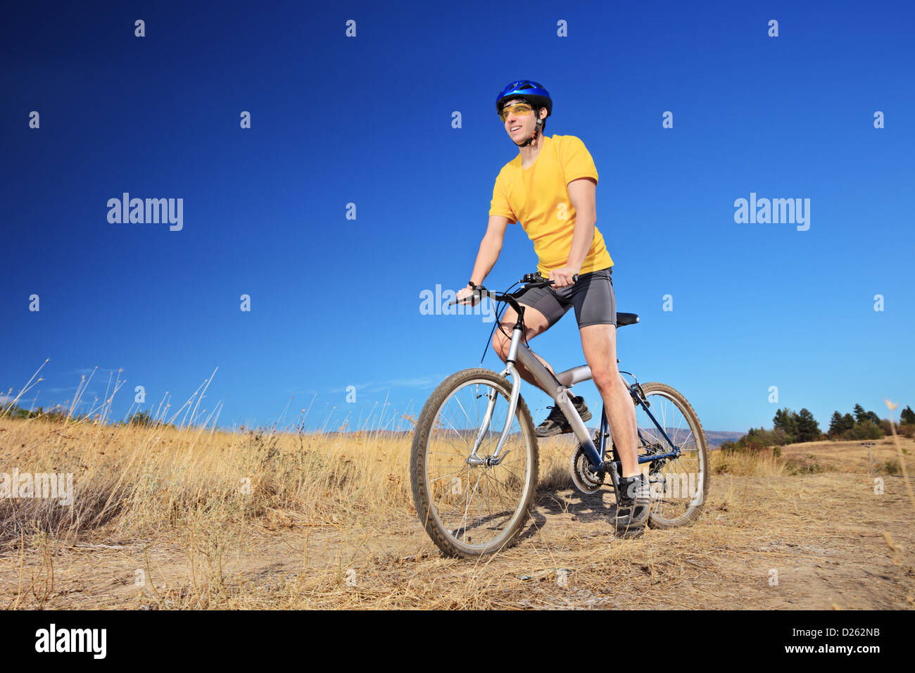 Panning shot of a bicycle rider riding a mountain bike outdoors on a sunny day against a blue sky - Stock Image