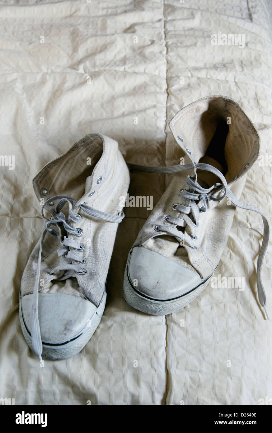 pair of old tennis shoes sitting on a bed. - Stock Image