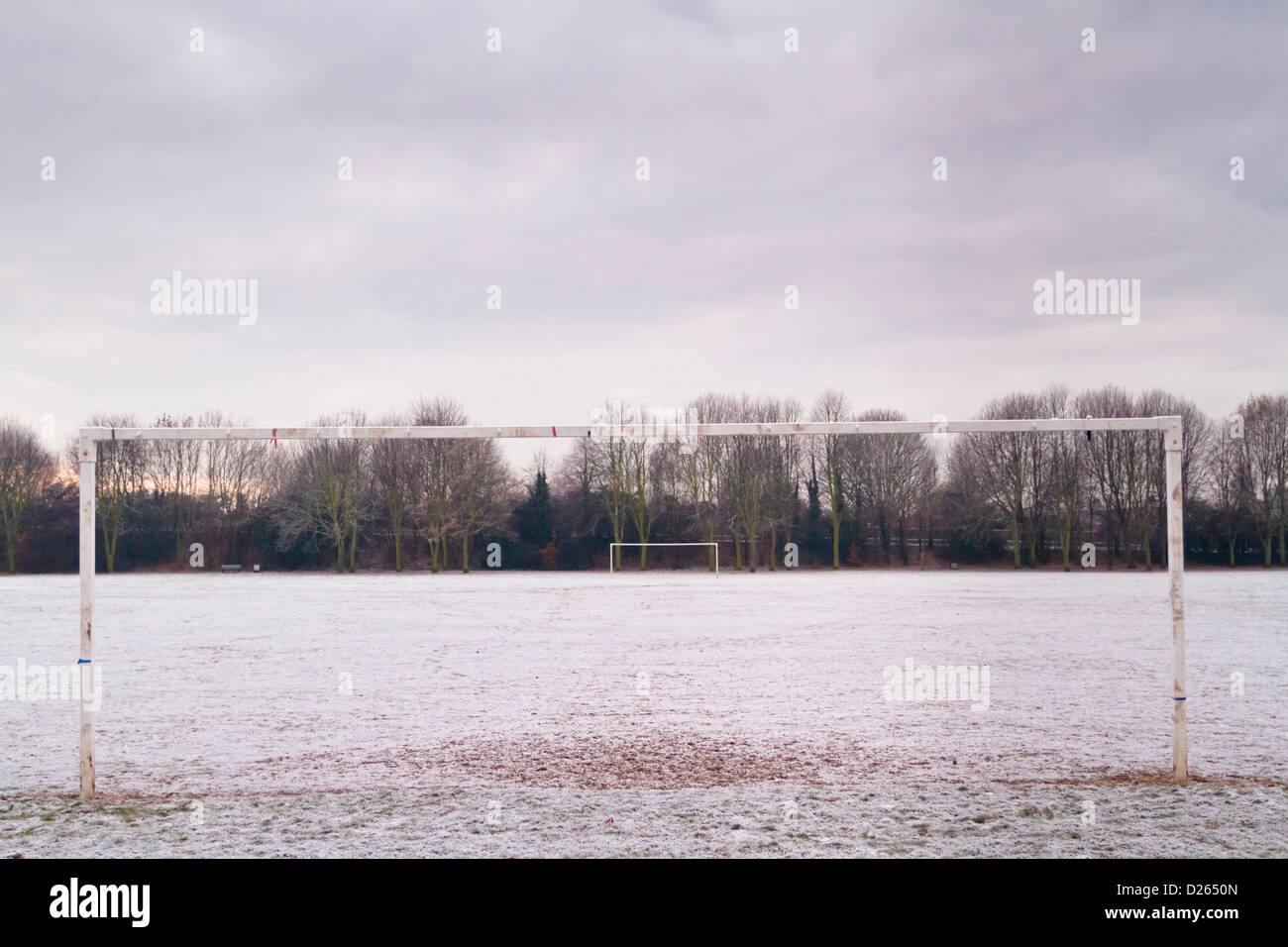 Goalpost on an empty football pitch on a snow covered public park at the end of a cold winter day, Nottinghamshire, - Stock Image