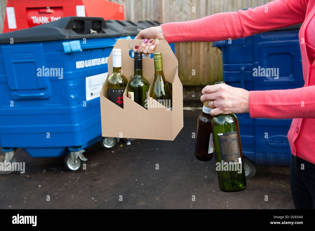 Woman recycles wine bottles at a recycling centre - Stock Image