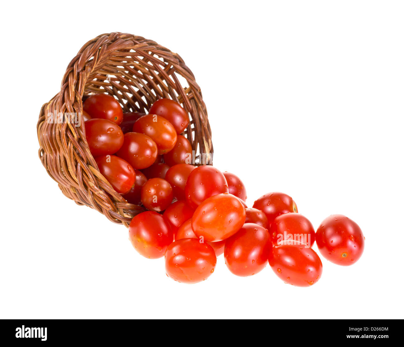 Several small grape tomatoes spilling from a wicker basket onto a white background. - Stock Image