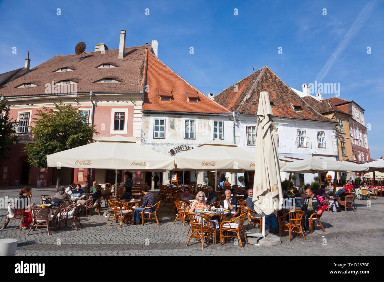 Sibiu, Hermannstadt in Transylvania, buildings on Piata Mica, locals enjoy Sunday morning having a coffee Stock Photo