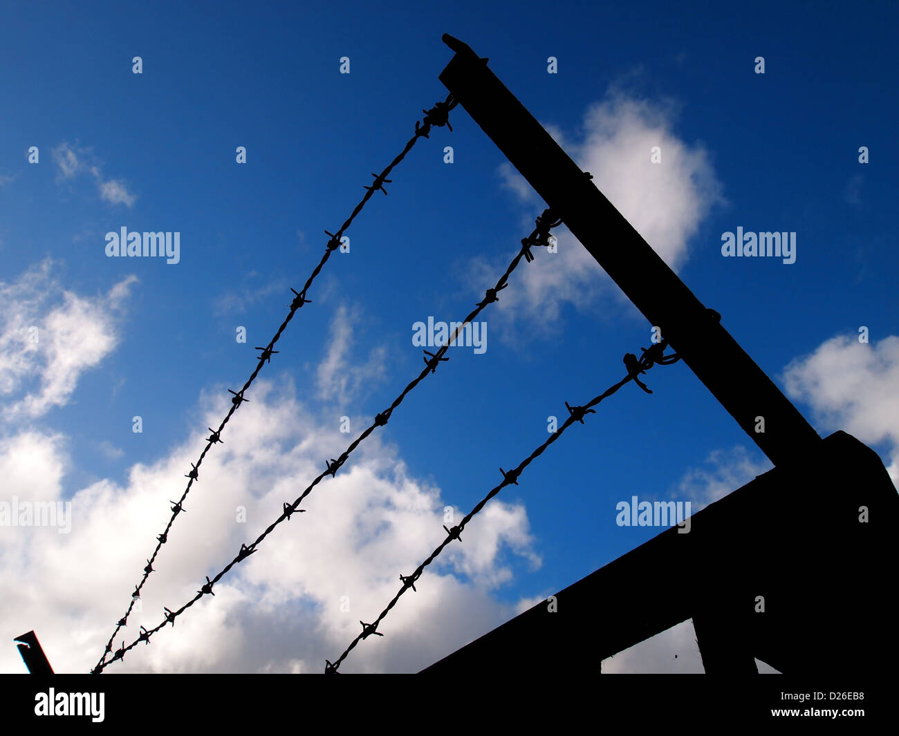 A barbed wire fence silhouetted against a blue sky. - Stock Image
