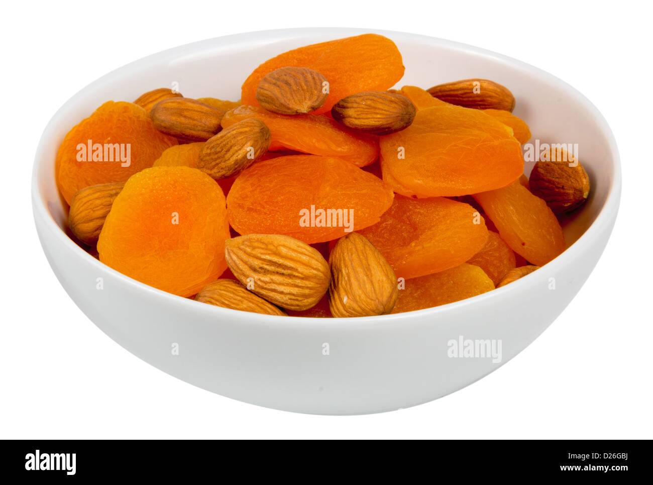Mixed almonds and dried apricots isolated on white - Stock Image