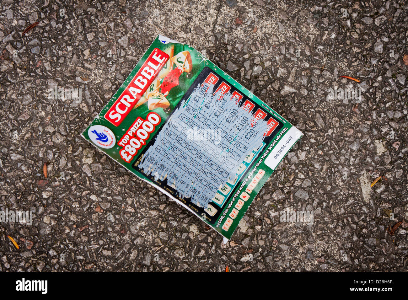 A losing scratchcard from the UK National Lottery has been thrown away on the road. - Stock Image