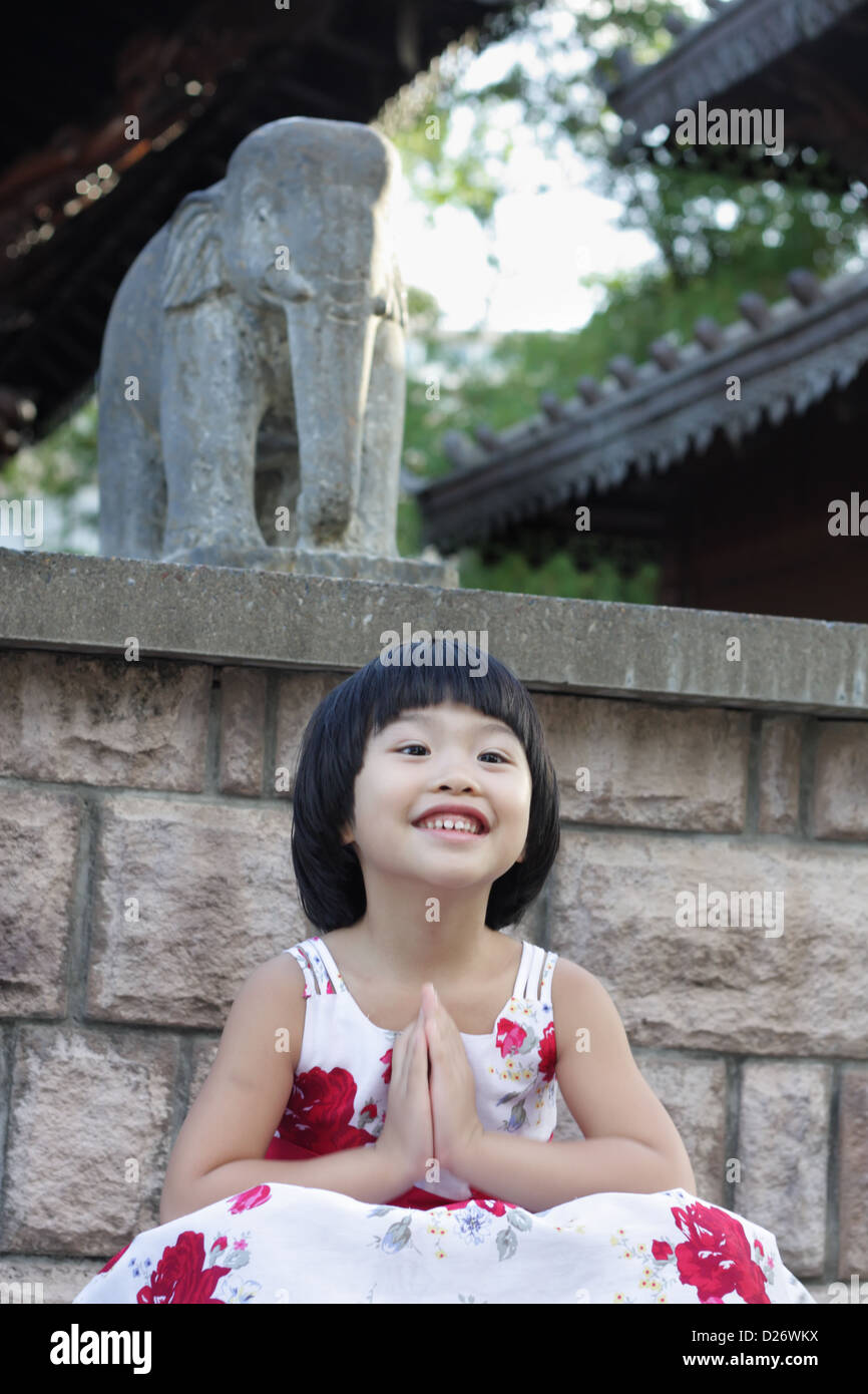 Pretty Bright Girl was sitting in Lotus Position with Praying Pose - Stock Image