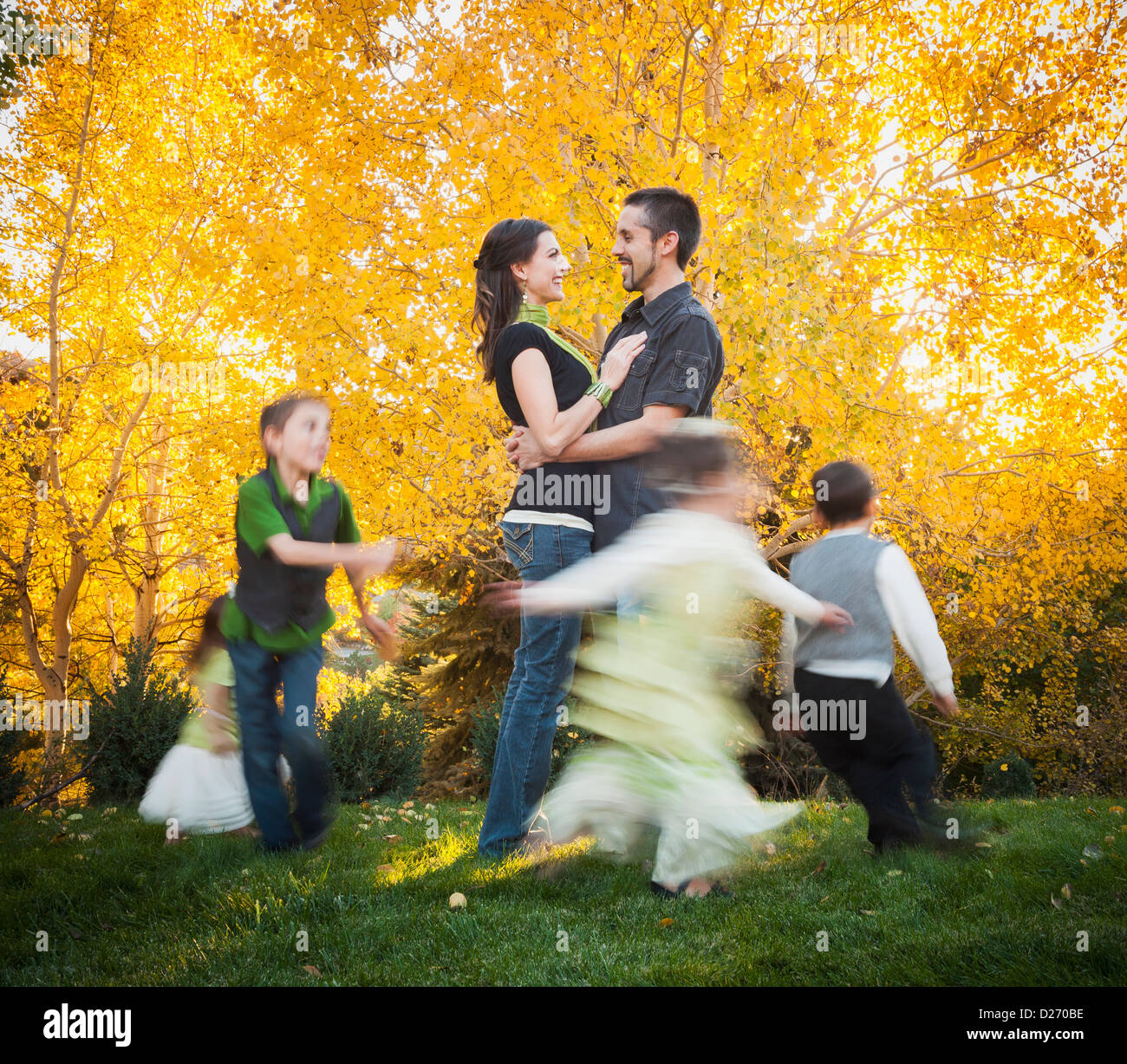 USA, Utah, Bountiful, Family with children (2-3, 4-5, 6-7, 8-9) dancing in garden at autumn - Stock Image