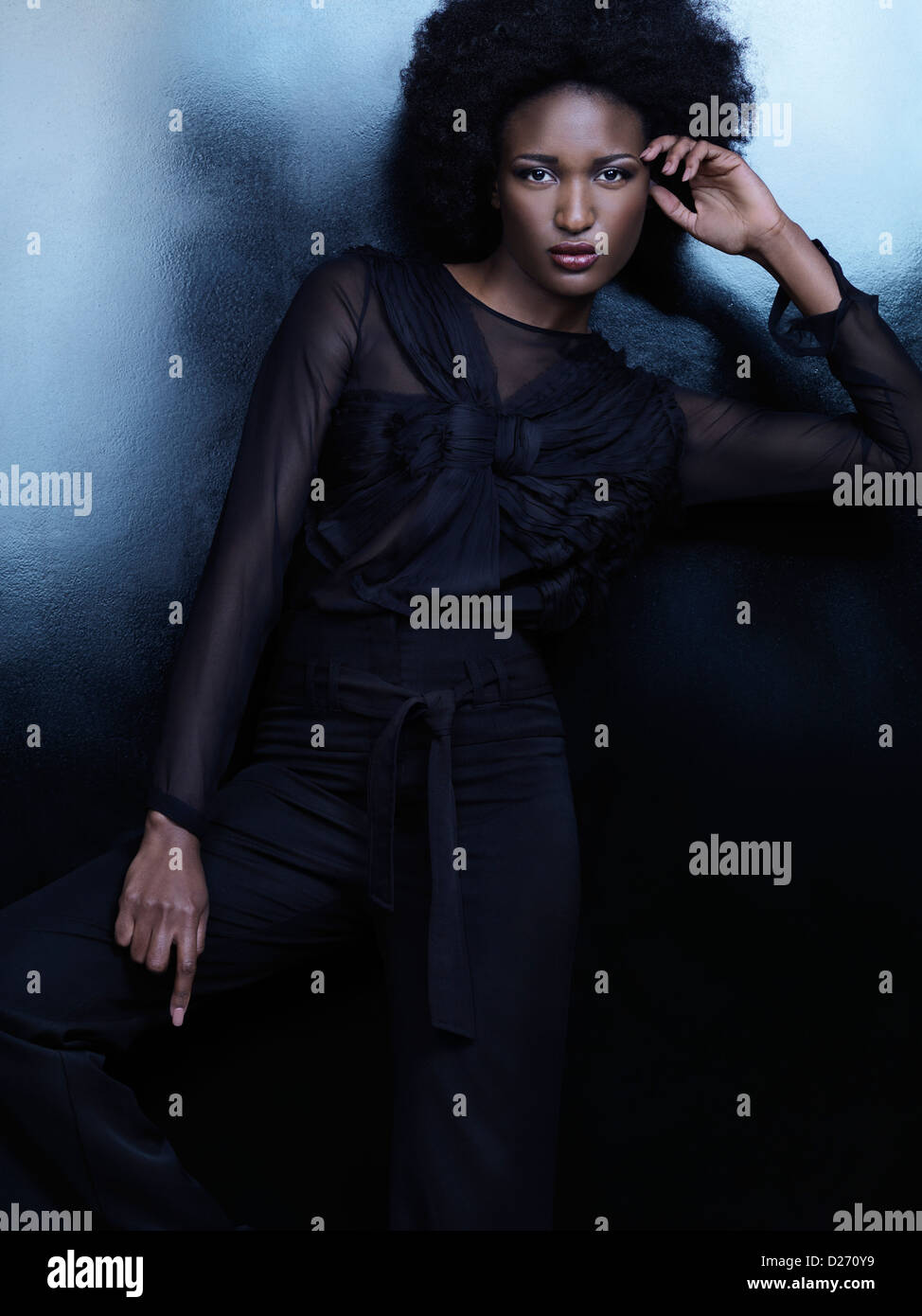 f87ebd2d0d0 Beautiful african american woman wearing fashionable black clothes posing  on shiny black background. High fashion photo.