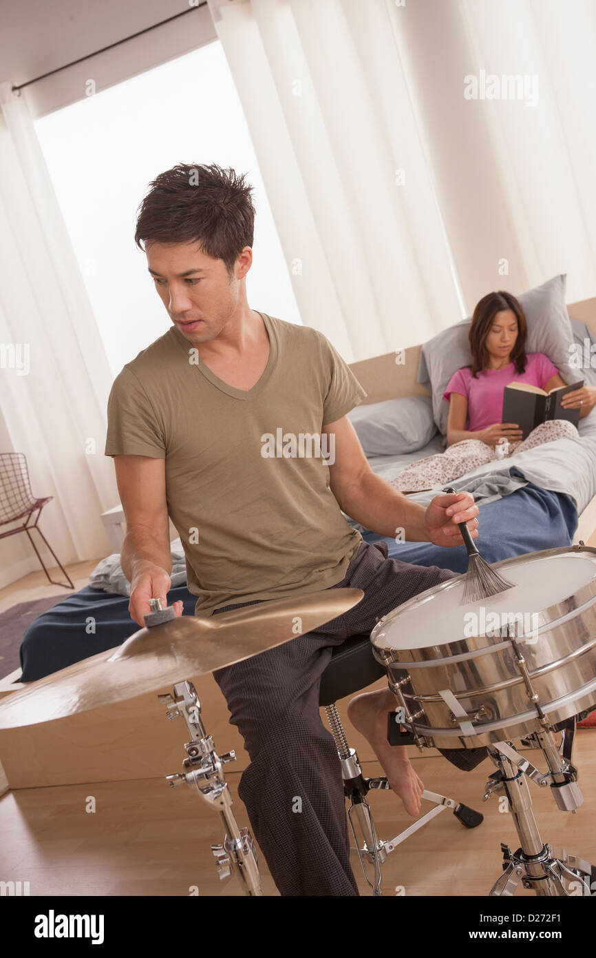 Man plying drums and woman reading in bed - Stock Image