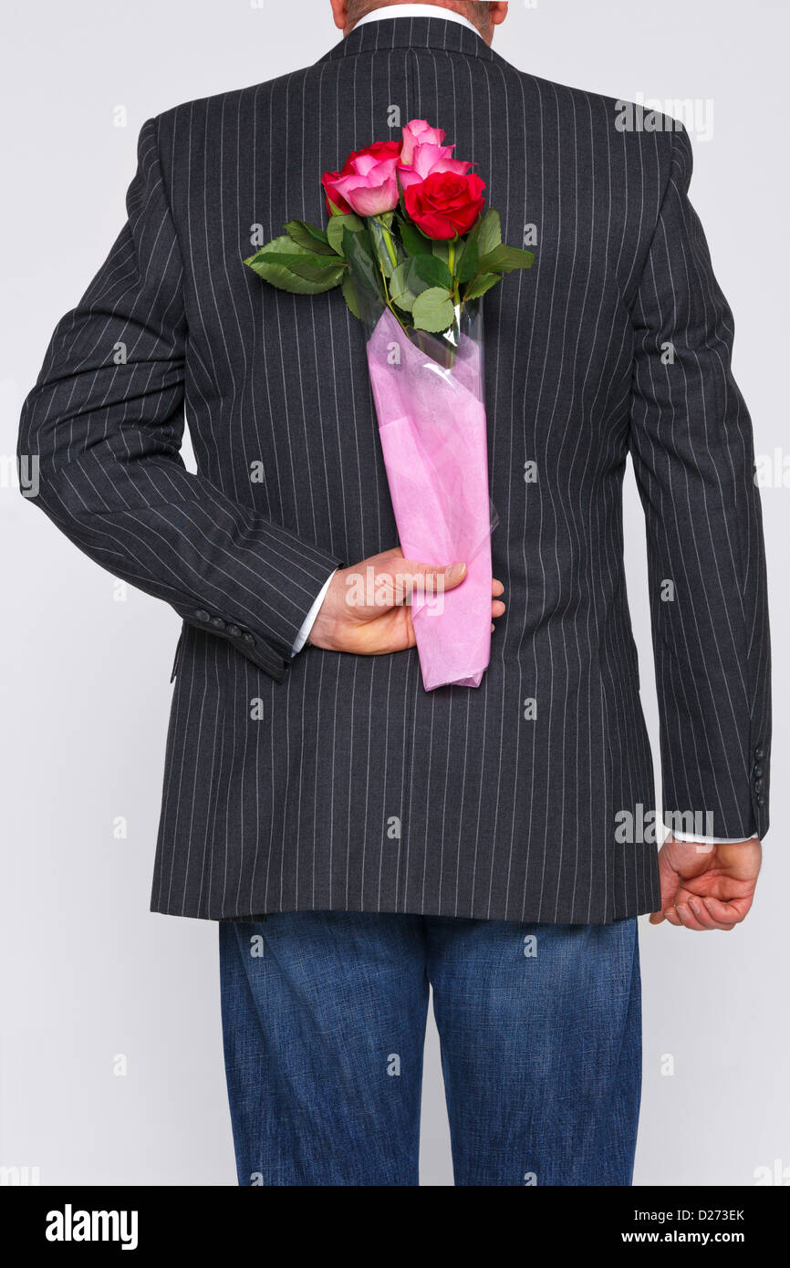 A man with a bunch of roses behind his back, the flowers are a surprise for someone. - Stock Image