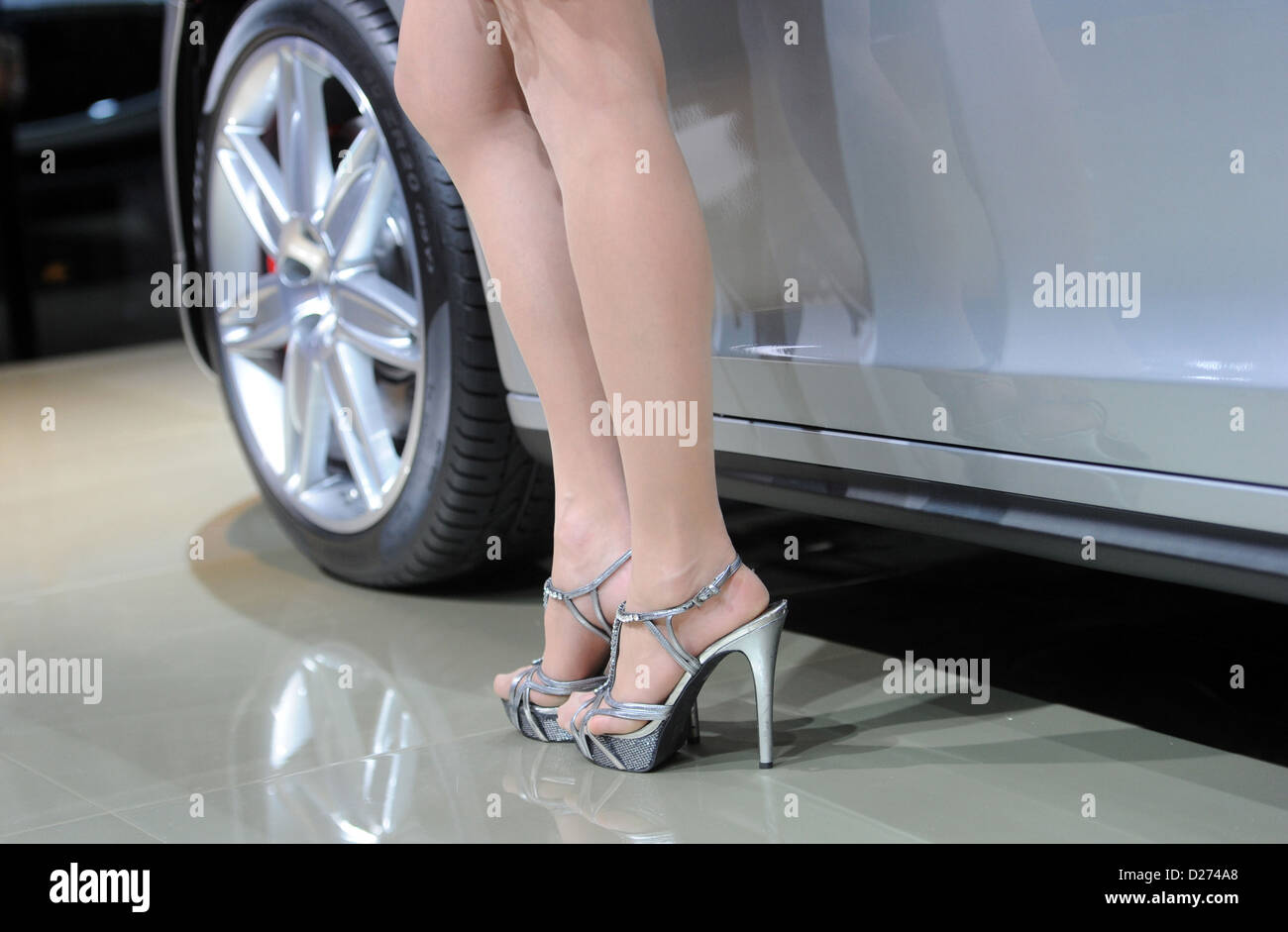 A Presenter Stands Next To Maserati Quattroporte Car Model During A - Car show wheel stands