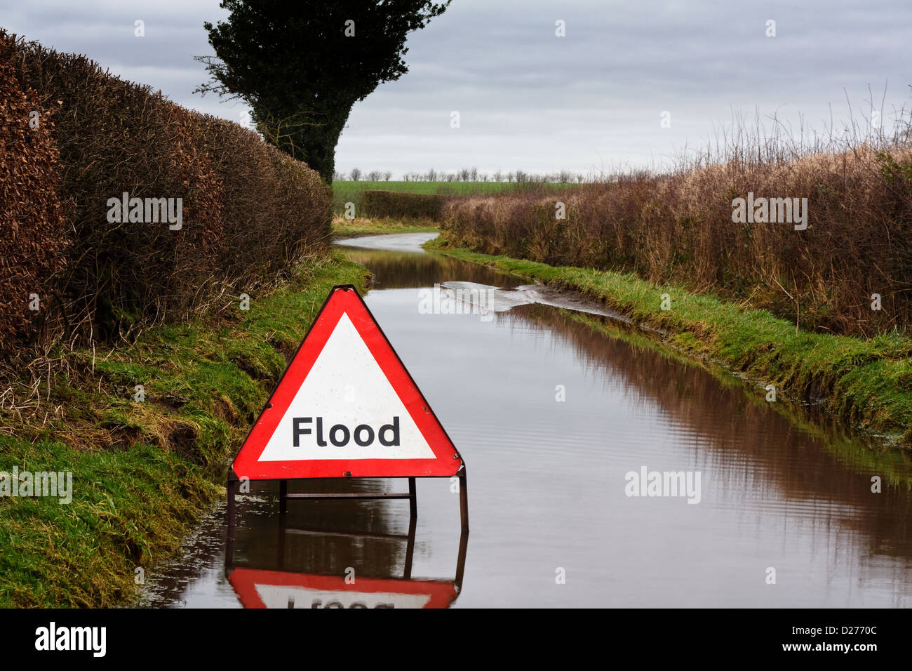 Flood warning sign on a flooded country road showing adverse driving conditions - Stock Image