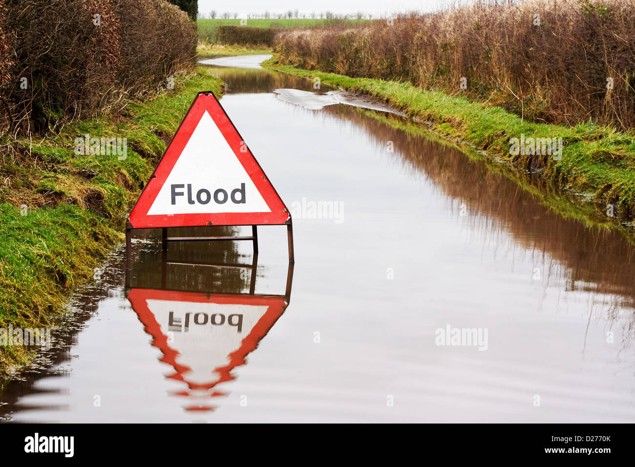 Flood warning sign on a flooded country road - Stock Image