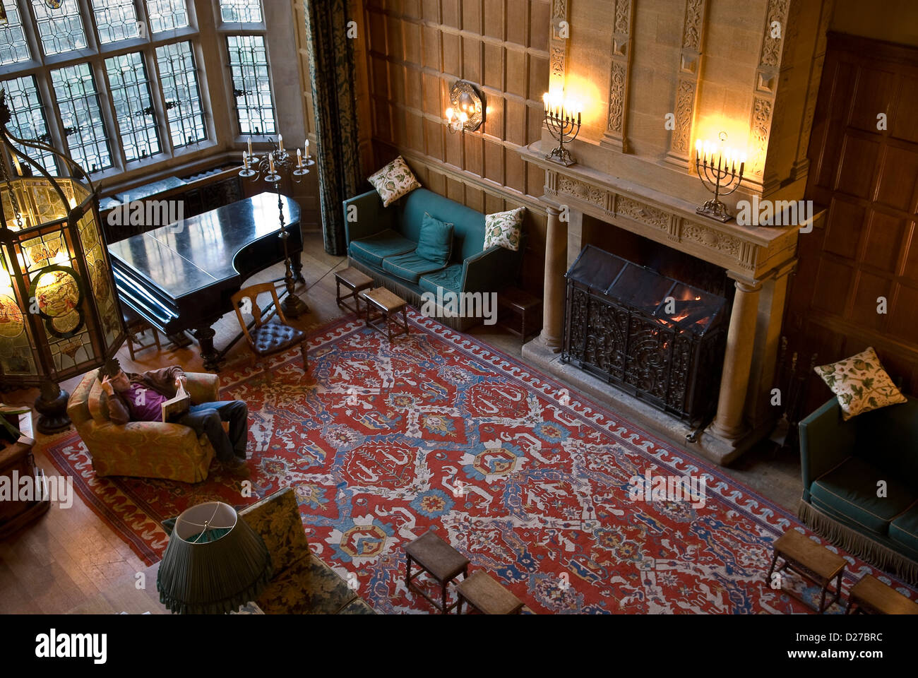 Student reading and relaxing by the fireside in the main hall at West Dean College, Chichester, West Sussex, UK - Stock Image