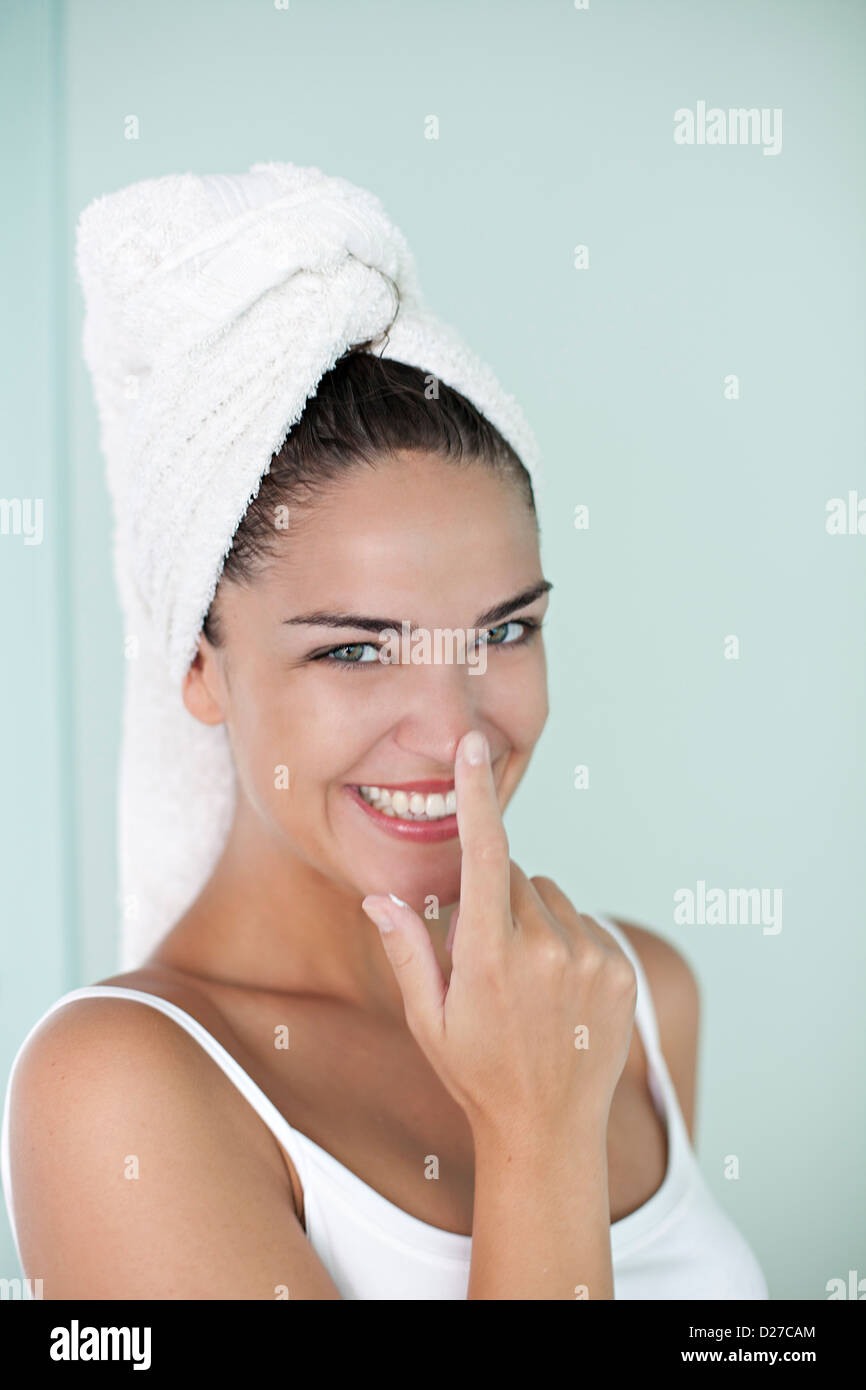 Brunette woman applying anti wrinkle cream after the shower - Stock Image